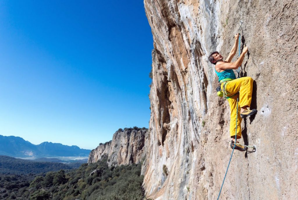 Mature male extreme Climber moving up on rocky Wall