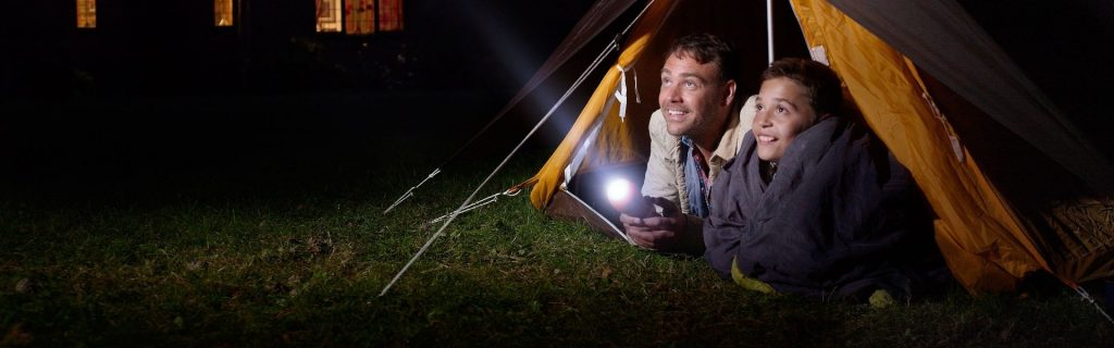 father-and-son-in-tent-shining-torch-in-distance--152821184-5be377e3c9e77c002612020d
